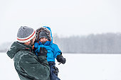 Father and Son Playing Outdoor in Winter Forest Snowstorm