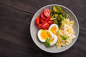 Farfalle pasta with egg, tomato and broccoli in a bowl