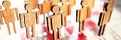 Little wooden toy people figures stand in row