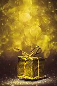 Golden metallic gift pack on glittery golden background.