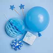 Party or birthday background. Balloon, gift box on blue background top view. Flat lay style.