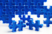 Pieces from a blue jigsaw puzzle arranged to form a page on white background. Break barriers together for autism concept