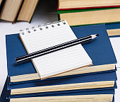 empty notebook with white sheets and a black pencil
