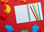 open notebook with empty white sheets and multicolored wooden pencils