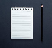notebook with white sheets in line and black wooden pencil