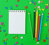 open notebook with blank white sheets in line, colored wooden pencils
