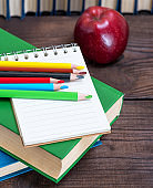 empty open notebook and multicolored wooden pencils