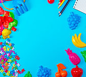 Blue background with childrens plastic toys, pencils, balloons and wooden letters