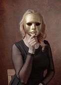Beautiful  woman with gold carnival mask.