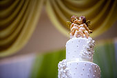 Wedding cake decorate with Cupid doll.Figurines of the bride and groom on a wedding cake