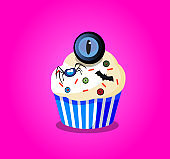 Cute happy halloween cupcake with spider, monster eyes and bat