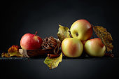 Juicy apples and cinnamon sticks on a black background.