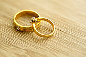 Wedding rings on wooden surface, symbol of wedding and couple