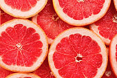Grapefruit red juicy slices background. top view