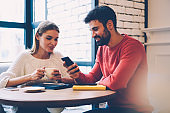 Smiling romantic couple watching video on smartphone while enjoying spending time together on coffee break, bearded guy showing photos on mobile to his pretty girlfriend communicating during date
