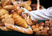 Close up chef arranging variety of fresh breads