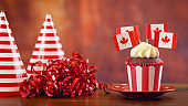 Red and white theme cupcakes with Canadian maple leaf flags