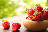 Ripe strawberry in a bowl on wooden surface, spring / summer, green tree leaves background.