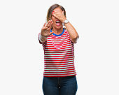 Middle age senior hispanic woman over isolated background covering eyes with hands and doing stop gesture with sad and fear expression. Embarrassed and negative concept.