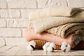 Minimalistic rustic composition with stacked vintage knitted easy chic oversized style sweaters, knitwear outfit.