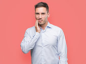 Handsome young businessman touching mouth with hand with painful expression because of toothache or dental illness on teeth. Dentist concept.
