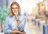 Young caucasian business woman wearing glasses over isolated background looking stressed and nervous with hands on mouth biting nails. Anxiety problem.