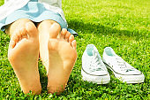 Female bare feet on mawed lawn grass. Young woman resting outdoors barefoot, take a break concept. Student on college campus yard.