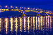 an automobile bridge across the Volga River at night, illuminated by the light of lanterns, the light of which is reflected in the river