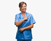 Middle age senior nurse doctor woman over isolated background cheerful with a smile of face pointing with hand and finger up to the side with happy and natural expression on face looking at the camera.