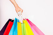 Multiple shopping bags of different color in female model's hand.