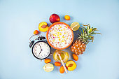 morning breakfast, muesli, fruit, peaches , ananas ,honey on a blue background Awakening with an alarm clock Healthy breakfast freshness Flat lay Top view Copyspace
