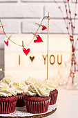 I love you written on a decorative lamp next to red cupcakes, red velvet with mascarpone cream. Valentine's day concept