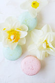 Traditional French blueberry strawberry cranberry macaroons dessert biscuits with beautiful flowers arrangement on white gray concrete textured background table top. Tasty but unhealthy food.