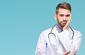 Young handsome doctor man over isolated background thinking looking tired and bored with depression problems with crossed arms.