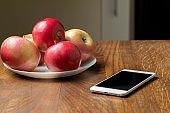 Smartphone on a wooden table near a plate with red apples.