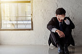 Young asian businessman sitting by the window feel stressed and depressed from work.