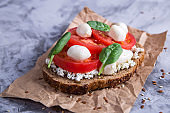 Beautiful healthy snack - sandwich with tomato, mozzarella and spinach leaves. Vegetarian food concept