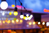 Decorative outdoor string lights hanging on electricity post in the garden at night time with blur people. Christmas,festival, holiday and wedding concepts.