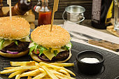 Delicious homemade hamburger served with French fries on wooden background. Delicious burger with onion, tomato, cheese and lettuce. Fast food meal. Rustic style