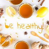 Be healthy - written from ground turmeric on a white background among the products for the treatment of common cold - lemon, honey, ginger