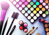 Professional make up set: eyeshadow palette, lipstick, make-up brushes and many cosmetics close up. Film and flare effect. Top view, flatlay