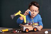 Elementary age school boy builds robot