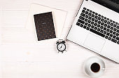 Blogger / businessman / businesswoman, it specialist's white wood office space table with laptop, blank screen smartphone, coffee cup and supplies. Top view, copy space, flat lay, overhead, backdrop.