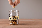 Pension. Glass jar with coins and an inscription pension. Man holds  coin in his hand