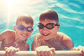 Two young boys holding edge of swimming pool