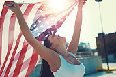 Happy young woman holding USA flag in air
