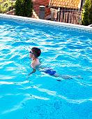 Little boy swim breaststroke in swimming pool
