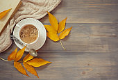 Cup of coffee with milk in sunny autumn day