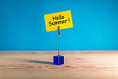 Hello Summer - text on a little yellow tag on blue bright background. First summer day. Happy Childrens Day
