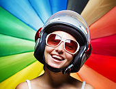 Funny girl in helmet having fun. Multicolored background